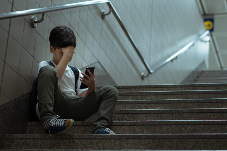 young asian teenage boy sitting stair covering his face with hand